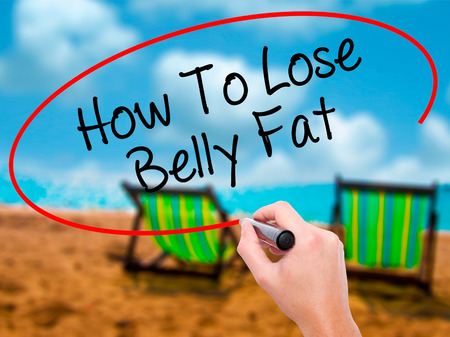 Man Hand writing How To Lose Belly Fat with black marker on visual screen. Isolated on sunbed on the beach. Business, technology, internet concept. Stock Photo