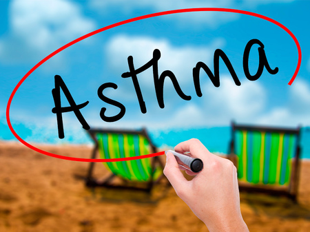 Man Hand writing Asthma with black marker on visual screen. Isolated on sunbed on the beach. Business, technology, internet concept. Stock Image