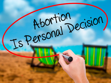 abortion womb: Man Hand writing Abortion Is Personal Decision with black marker on visual screen. Isolated on sunbed on the beach. Business, technology, internet concept. Stock Photo