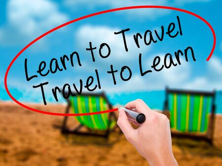 positiveness: Man Hand writing Learn to Travel. Travel to Learn with black marker on visual screen. Isolated on sunbed on the beach. Travel, technology, internet concept. Stock Image