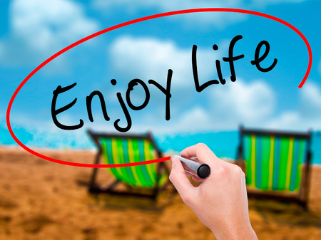 Man Hand writing Enjoy Life with black marker on visual screen. Isolated on sunbed on the beach. Business, technology, internet concept. Stock Photo