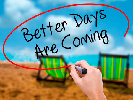 Man Hand writing Better Days Are Coming with black marker on visual screen. Isolated on sunbed on the beach. Business, technology, internet concept. Stock  Photo