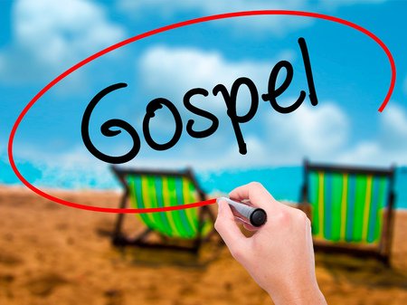 credo: Man Hand writing Gospel  with black marker on visual screen. Isolated on sunbed on the beach. Business, technology, internet concept. Stock Photo