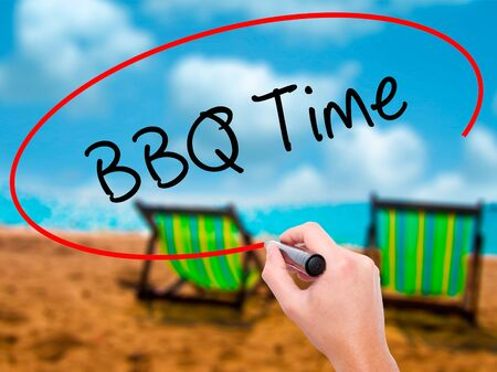 Man Hand writing BBQ Time with black marker on visual screen. Isolated on sunbed on the beach. Business, technology, internet concept. Stock Photo