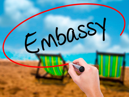 Man Hand writing Embassy with black marker on visual screen. Isolated on sunbed on the beach. Business, technology, internet concept. Stock Photo Stock Photo