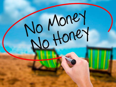Man Hand writing No Money No Honey with black marker on visual screen. Isolated on sunbed on the beach. Business, technology, internet concept. Stock Photo