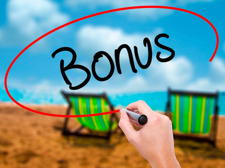 additional compensation: Man Hand writing Bonus with black marker on visual screen. Isolated on sunbed on the beach. Business, technology, internet concept. Stock Photo