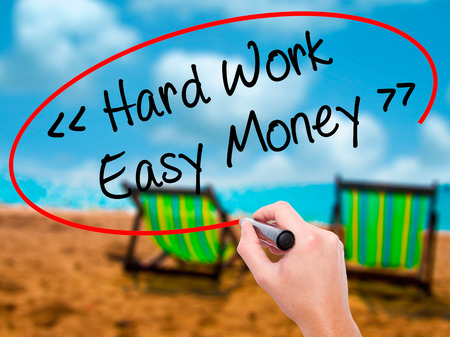 Man Hand writing Hard Work - Easy Money with black marker on visual screen. Isolated on sunbed on the beach. Business, technology, internet concept. Stock Photo
