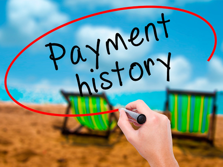 Man Hand writing Payment history with black marker on visual screen. Isolated on sunbed on the beach. Business, technology, internet concept. Stock Image