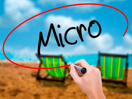 Man Hand writing Micro with black marker on visual screen. Isolated on sunbed on the beach. Business, technology, internet concept. Stock Photo