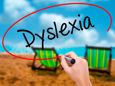 Man Hand writing Dyslexia with black marker on visual screen. Isolated on sunbed on the beach. Business, technology, internet concept. Stock Photo