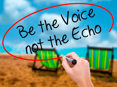 to be or not be: Man Hand writing Be the Voice not the Echo with black marker on visual screen. Isolated on sunbed on the beach. Business, technology, internet concept. Stock Photo Stock Photo