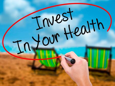 Man Hand writing Invest In Your Health with black marker on visual screen. Isolated on sunbed on the beach. Business, technology, internet concept. Stock Photo