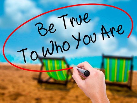 Man Hand writing Be True To Who You Are with black marker on visual screen. Isolated on sunbed on the beach. Business, technology, internet concept. Stock Photo Stock Photo