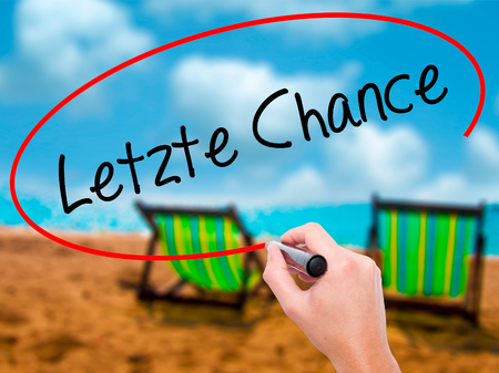 Man Hand writing Letzte Chance  (Last Chance in German) with black marker on visual screen. Isolated on sunbed on the beach. Business, technology, internet concept. Stock Photo