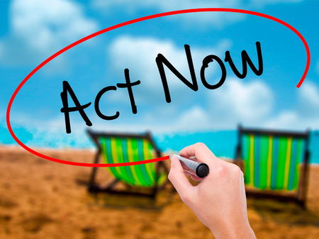 Man Hand writing Act Now with black marker on visual screen. Isolated on sunbed on the beach. Business, technology, internet concept. Stock Photo