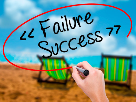 opt: Man Hand writing Failure Success with black marker on visual screen. Isolated on sunbed on the beach. Business, technology, internet concept. Stock Photo