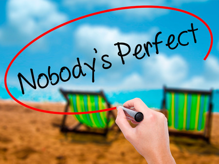 Man Hand writing Nobodys Perfect with black marker on visual screen. Isolated on sunbed on the beach. Business, technology, internet concept. Stock Photo