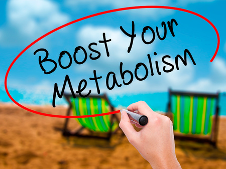 Man Hand writing Boost Your Metabolism with black marker on visual screen. Isolated on sunbed on the beach. Business, technology, internet concept. Stock Image Stock Photo