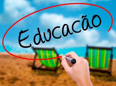 Man Hand writing Education (Educacao in Portuguese) with black marker on visual screen. Isolated on sunbed on the beach. Business, technology, internet concept. Stock Photo