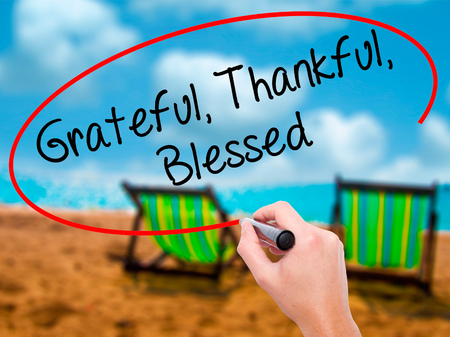 Man Hand writing  Grateful Thankful Blessed with black marker on visual screen. Isolated on sunbed on the beach. Business, technology, internet concept. Stock Photo
