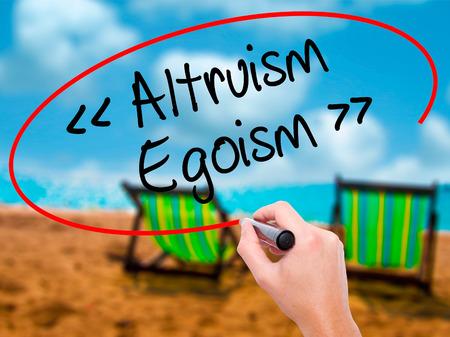 altruismo: Hombre de la mano de escritura Altruismo - Egoísmo con marcador negro en la pantalla visual. Aislado en el baño de sol en la playa. Negocios, la tecnología, el concepto de internet. Foto de stock Foto de archivo