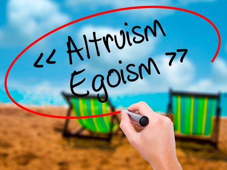 altruism: Man Hand writing Altruism - Egoism with black marker on visual screen. Isolated on sunbed on the beach. Business, technology, internet concept. Stock Photo