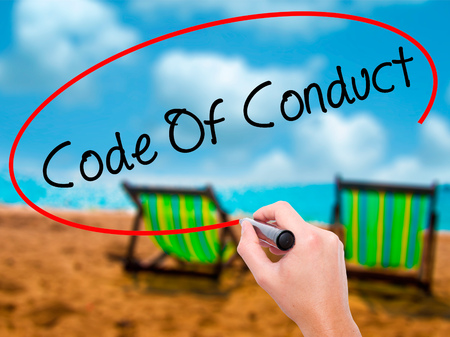 work ethic responsibilities: Man Hand writing Code Of Conduct with black marker on visual screen. Isolated on sunbed on the beach. Business, technology, internet concept. Stock Photo