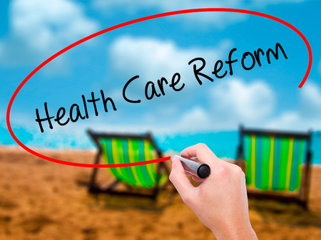 Man Hand writing Health Care Reform with black marker on visual screen. Isolated on sunbed on the beach. Business, technology, internet concept.