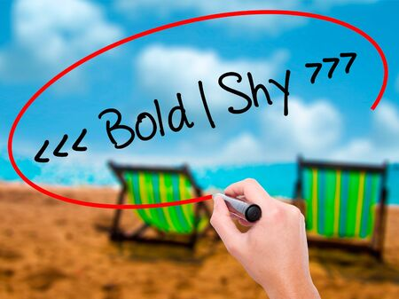 extrovert: Man Hand writing Bold - Shy  with black marker on visual screen. Isolated on sunbed on the beach. Business, technology, internet concept. Stock Photo
