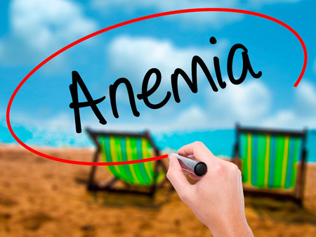 Man Hand writing Anemia  with black marker on visual screen. Isolated on sunbed on the beach. Business, technology, internet concept. Stock Photo Stock Photo