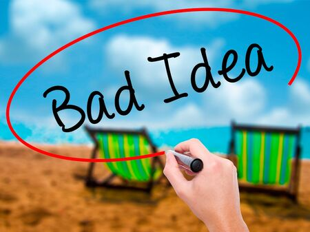 deficient: Man Hand writing Bad Idea with black marker on visual screen. Isolated on sunbed on the beach. Business, technology, internet concept. Stock Photo