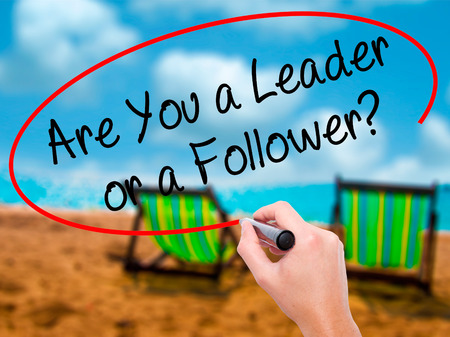 blindly: Man Hand writing Are You a Leader or a Follower? with black marker on visual screen. Isolated on sunbed on the beach. Business, technology, internet concept. Stock Photo