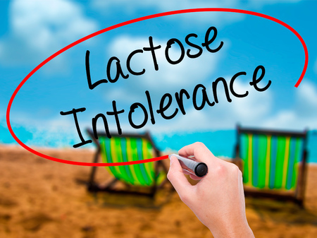 intolerance: Man Hand writing Lactose Intolerance with black marker on visual screen. Isolated on sunbed on the beach. Business, technology, internet concept. Stock Photo Foto de archivo