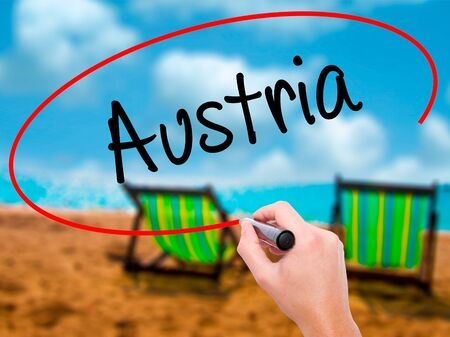 Man Hand writing  Austria with black marker on visual screen. Isolated on sunbed on the beach. Business, technology, internet concept. Stock Photo Stock Photo