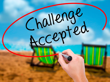 Man Hand writing  Challenge Accepted with black marker on visual screen. Isolated on sunbed on the beach. Business, technology, internet concept. Stock Photo