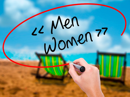 Man Hand writing Men - Women with black marker on visual screen. Isolated on sunbed on the beach. Business, technology, internet concept. Stock Photo