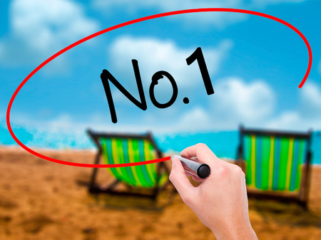 Man Hand writing No.1 with black marker on visual screen. Isolated on sunbed on the beach. Business, technology, internet concept. Stock Photo Stock Photo