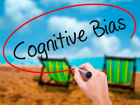 cognicion: Hombre de la mano escribiendo prejuicio cognitivo con marcador negro en la pantalla visual. Aislado en el baño de sol en la playa. Negocios, la tecnología, el concepto de internet. Foto de stock