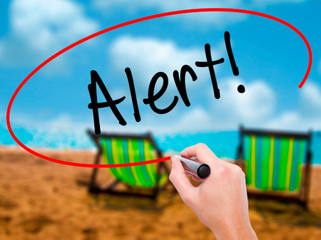 Man Hand writing Alert! with black marker on visual screen. Isolated on sunbed on the beach. Business, technology, internet concept. Stock Photo Stock Photo