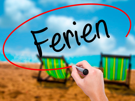 adjourned: Man Hand writing Ferien  (Vacation in German) with black marker on visual screen. Isolated on sunbed on the beach. Business, technology, internet concept. Stock Photo