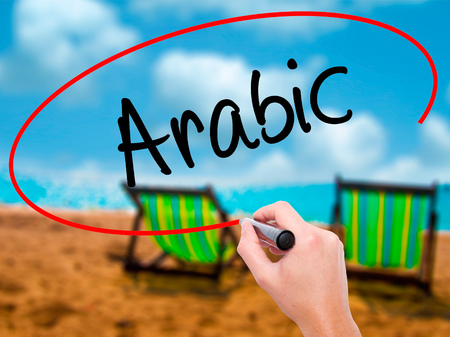 ethic: Man Hand writing Arabic  with black marker on visual screen. Isolated on sunbed on the beach. Business, technology, internet concept. Stock Photo