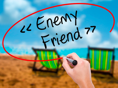 pretender: Man Hand writing Enemy - Friend with black marker on visual screen. Isolated on sunbed on the beach. Business, technology, internet concept. Stock Photo