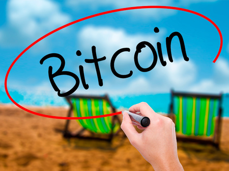 ltc: Man Hand writing Bitcoin with black marker on visual screen. Isolated on sunbed on the beach. Business, technology, internet concept. Stock Photo