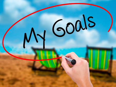 Man Hand writing  My Goals with black marker on visual screen. Isolated on sunbed on the beach. Business, technology, internet concept. Stock Photo