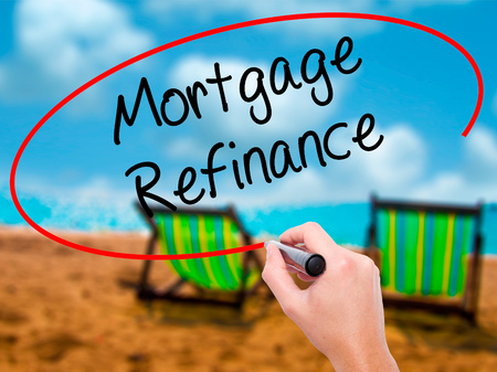 Man Hand writing Mortgage Refinance with black marker on visual screen. Isolated on sunbed on the beach. Business, technology, internet concept. Stock Photo