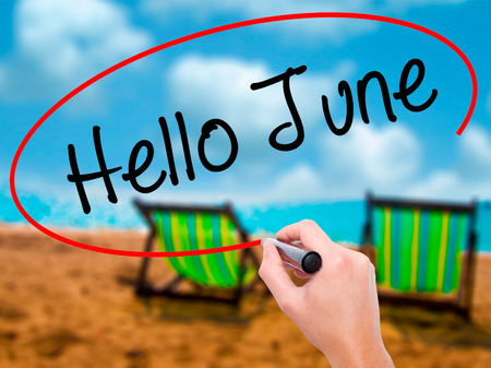 Man Hand writing Hello June  with black marker on visual screen. Isolated on sunbed on the beach. Business, technology, internet concept. Stock Photo