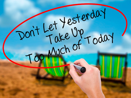 Man Hand writing Dont Let Yesterday Take Up Too Much of Today with black marker on visual screen. Isolated on sunbed on the beach. Business, technology, internet concept. Stock Photo