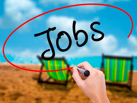 joblessness: Man Hand writing Jobs with black marker on visual screen. Isolated on sunbed on the beach. Business, technology, internet concept. Stock Image Stock Photo