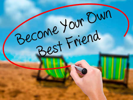 owning: Man Hand writing  Become Your Own Best Friend with black marker on visual screen. Isolated on sunbed on the beach. Business, technology, internet concept. Stock Photo Stock Photo
